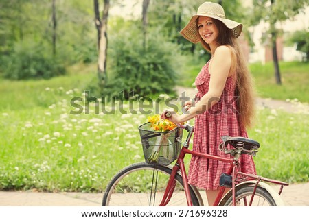 young woman in a dress and hat with a bike in a summer park. Active people. Outdoors - stock photo