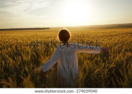 Young woman in a field of ripe wheat - stock photo