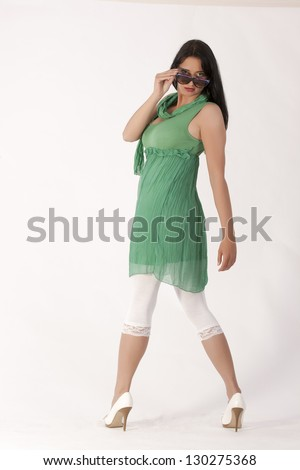 Young woman in a green tunic with leggings and sunglasses / Perfect ha ping - stock photo
