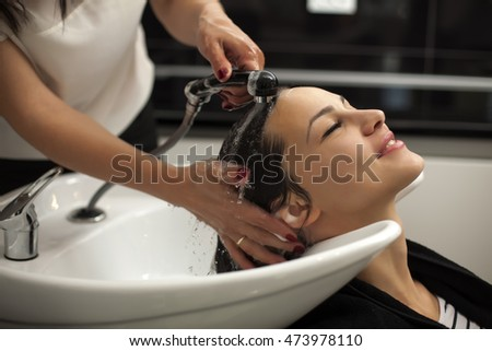 young woman in a hair salon enjoys washing her hair