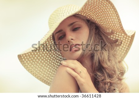 Young woman in a hat portrait. Yellow tint.