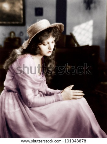 Young woman in a hat sitting and looking sad - stock photo