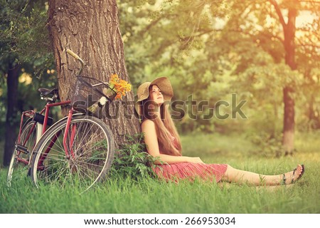 young woman in a hat with a bike sitting in the park near the tree . Active people. Outdoors - stock photo
