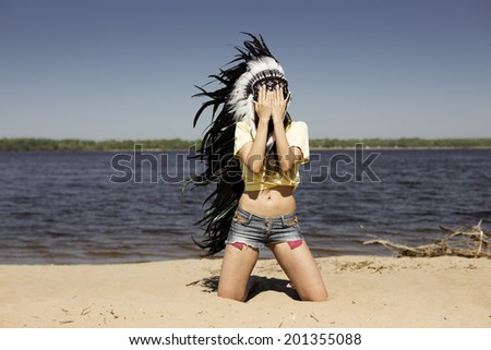 young woman in a headdress on the beach - stock photo