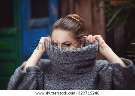 Young woman in a knitted turtleneck sweater covering her face. Close up - stock photo