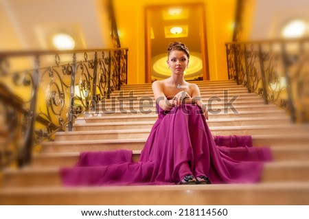 young woman in a long dress on the stairs in the hotel lobby - stock photo
