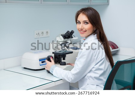 young woman in a medical lab with a microscope
