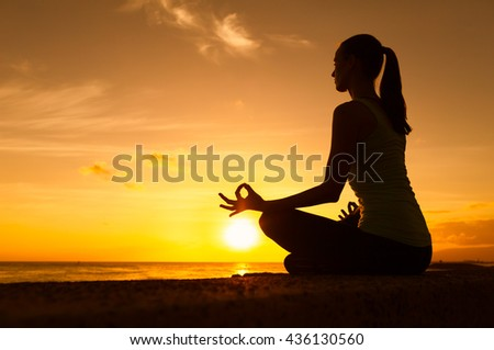 Young woman in a meditating yoga pose overlooking the beautiful sunset. Mind body spirit concept.  - stock photo