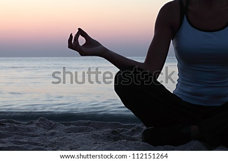 Young woman in a meditation on the beach - stock photo