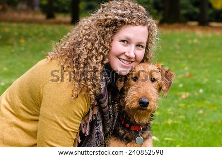 Young woman in a park with her dog.