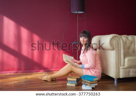 Young woman in a pink dress sitting on the floor next to the chair, with a book in his hand. Fashion photo shoot in the studio.