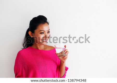 Young woman in a pink top drinking water and standing against a white wall - stock photo