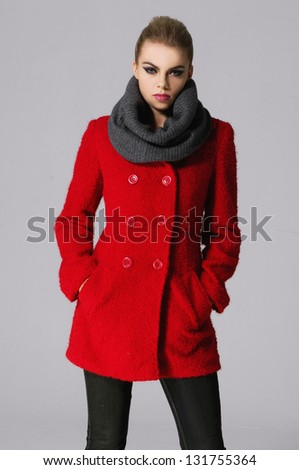 young woman in a red coat, scarf over gray background. - stock photo