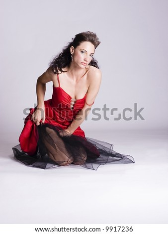 Young woman in a red dress kneeling on the floor
