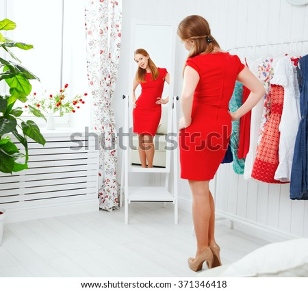 young woman in a red dress looks in the mirror and choose clothes - stock photo