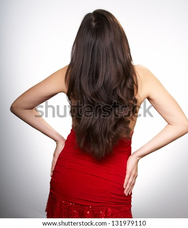 Young woman in a red dress with long dark hair. Woman standing her back to the camera. On a white background
