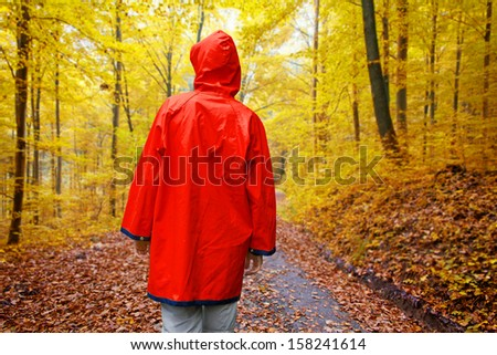 Young woman in a red raincoat walking in autumn