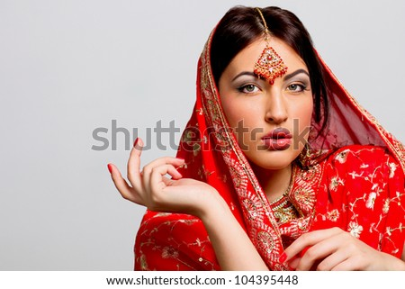 young woman in a red sari with a gray background