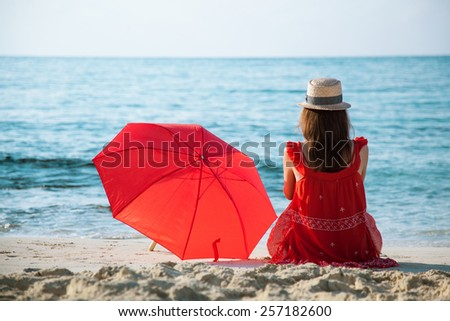 Young woman in a red sundress sitting on the sandy beach - stock photo