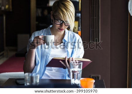 Young woman in a restaurant reading a book  - stock photo