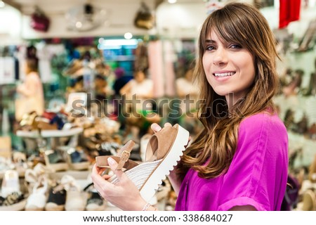 Young woman in a shoes shop, holding a shoe and smiling happy at the camera.