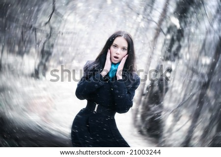 Young woman in a snowstorm. Background blur effect. - stock photo