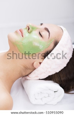 Young woman in a spa with algae facial mask