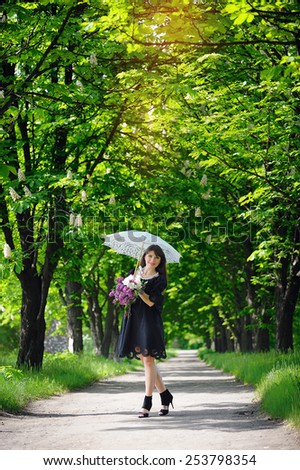 young woman in a spring park with an umbrella. - stock photo