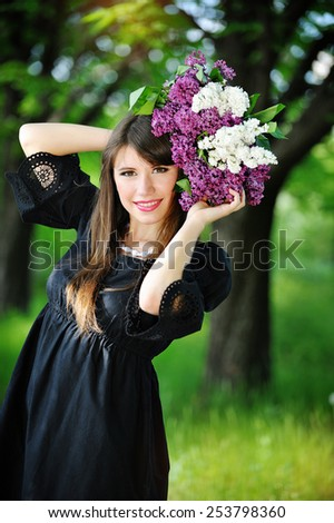 young woman in a spring park with lilac. - stock photo