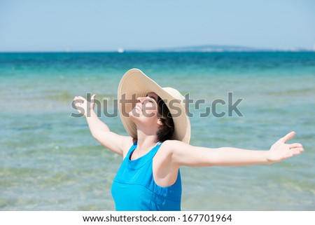 Young woman in a straw sunhat embracing the summer sun standing with her arms outspread, head tilted back and a smile of bliss on her face alongside the ocean - stock photo
