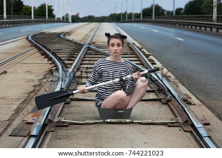 Young woman in a striped sailor's vest and with oar in hands in the middle of tram rails sits in tin little basin - strange place and device for navigation