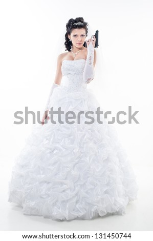 Young woman in a wedding dress with gun on a white background. bride. wedding. studio. - stock photo