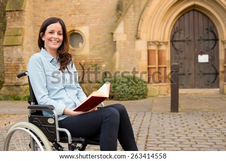 young woman in a wheelchair reading a bible outside a church - stock photo