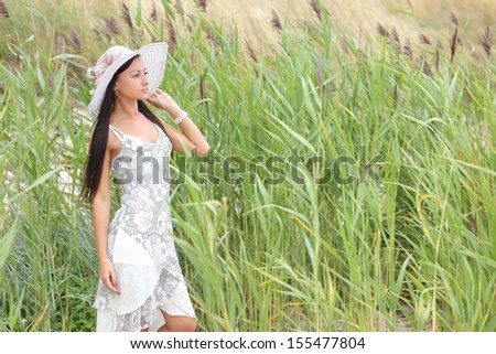 young woman in a white dress on a background of tall grass