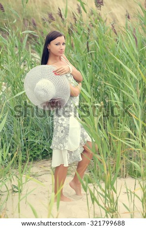 young woman in a white dress on a background of tall grass - stock photo