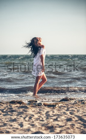 Young woman in a white dress on the beach