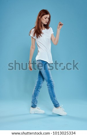 young woman in a white T-shirt in jeans in full growth on a blue background