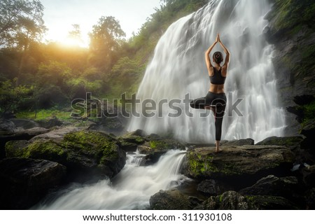 Young woman in a yoga pose at the waterfall - stock photo