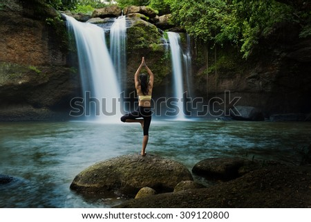 Young woman in a yoga pose at the waterfall, she felt relaxed. The exercise - stock photo