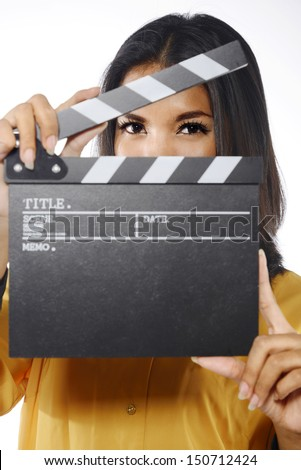 Young woman in action, holding clapperboard. Isolated over white background - stock photo