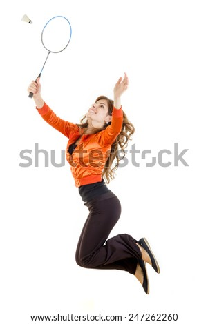 Young woman in action jumping with racket for badminton catching shuttlecock - stock photo