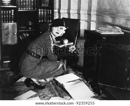 Young woman in an office next to a safe, looking over her shoulder - stock photo