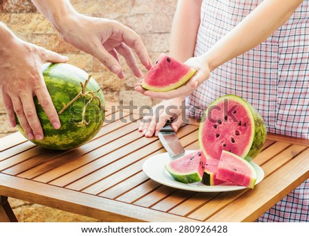 Young woman in apron giving to man a slice of fresh ripe juicy watermelon. Watermelons on a wooden table. Healthy eco sweet food rich in vitamins. Popular product of organic farming. - stock photo