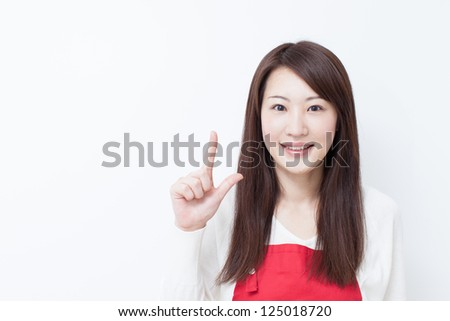 Young woman in apron showing copy space - stock photo
