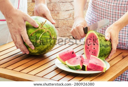 Young woman in apron slicing ripe watermelon on wooden table. Young man putting watermelon on table. Healthy eco food rich in vitamins. Product of organic farming. - stock photo