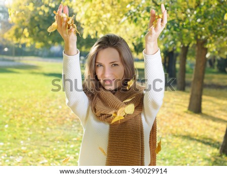 Young woman in autumn fall park playing throwing leaves - stock photo