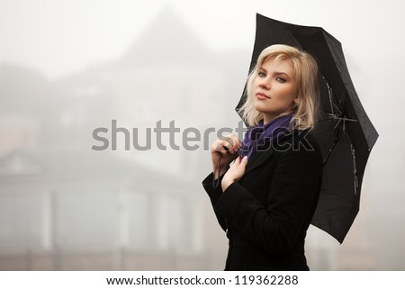 Young woman in autumn foggy morning - stock photo