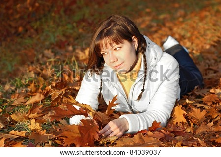 Young woman in autumn orange leaves in forest