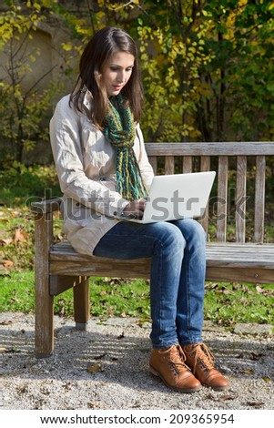 Young woman in autumn sitting on a park bench writing something with her laptop. - stock photo