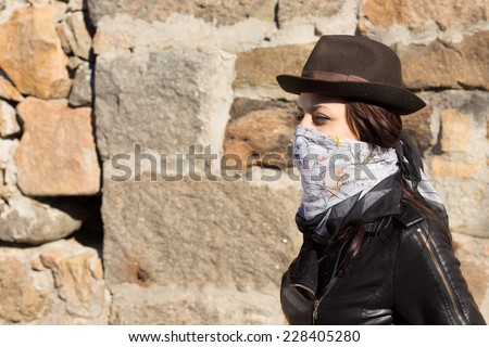 Young woman in bandit style fashion wearing a bandanna tied around her lower face in a trendy hat and leather jacket, side view in front of a stone wall - stock photo